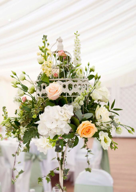 Peach and mint wedding flowers bird cage table display Parklands Quendon Hall Essex
