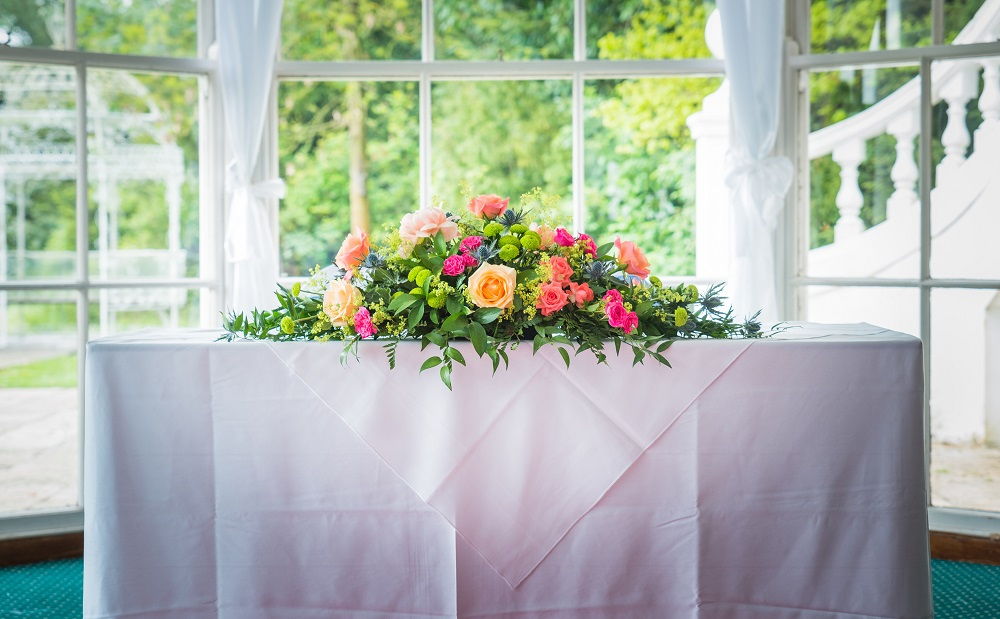 Vibrant coral pink lime and navy wedding flowers top table display at Manor of Groves Hertfordshire