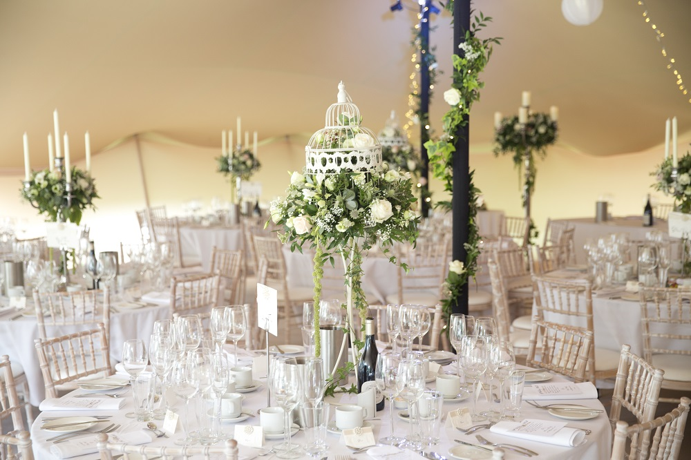 Enchanted secret garden wedding flowers table displays birdcages Hertfordshire Widford Church Much Hadham Marquee