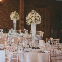 The all white table decorations featuring lisianthus, roses, gypsophila and hydrangea