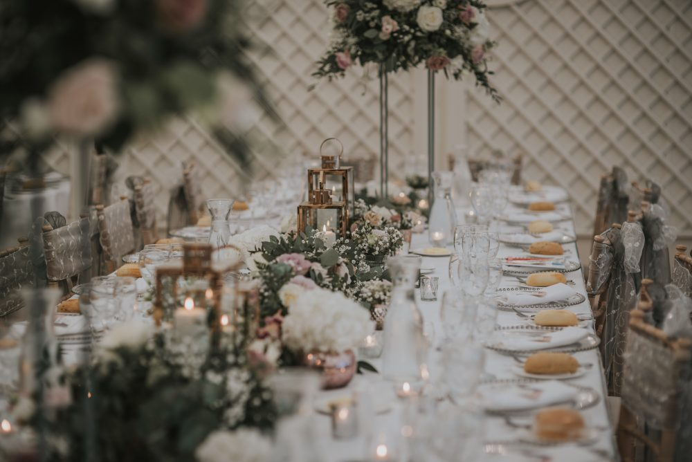 Rose gold lanterns stand out against the grey and dusky pink wedding flowers.